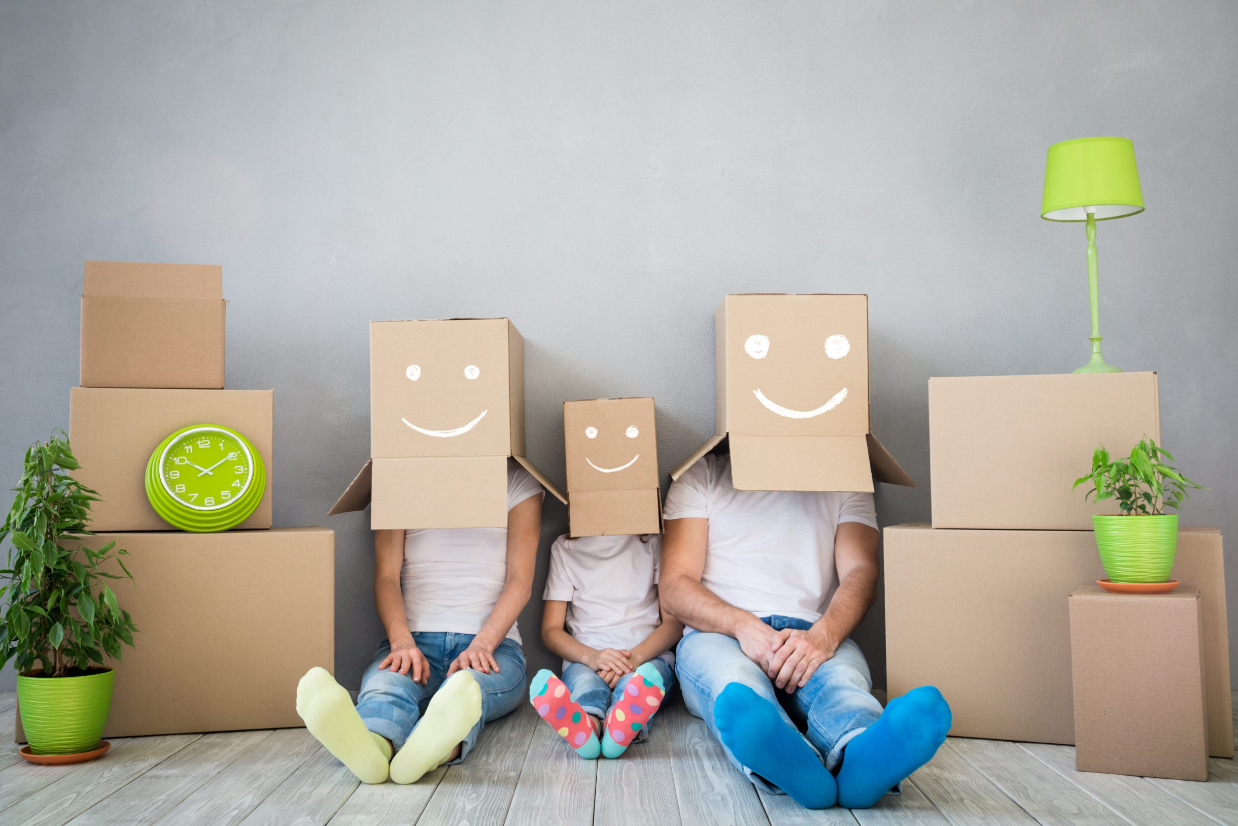 Ein Bild von drei Kindern die Umzugskartons als Mützen tragen